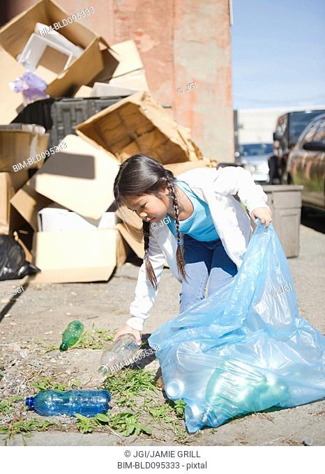 Korean girl picking up plastic bottles