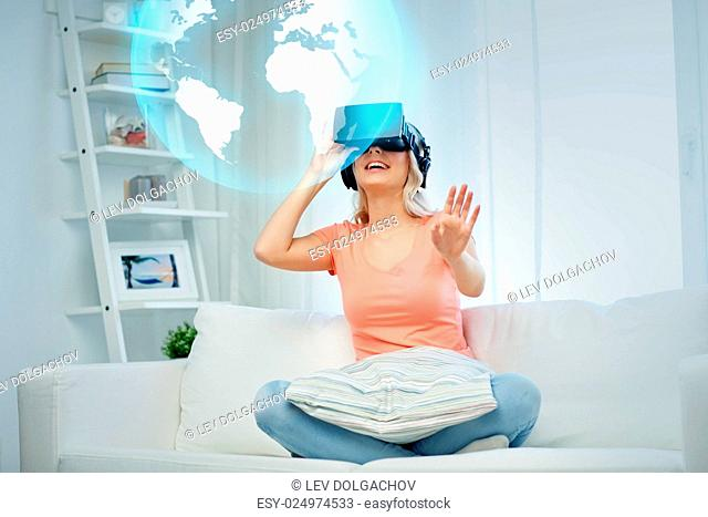 technology, augmented reality, entertainment and people concept - happy young woman in virtual headset or 3d glasses and headphones playing game at home looking...