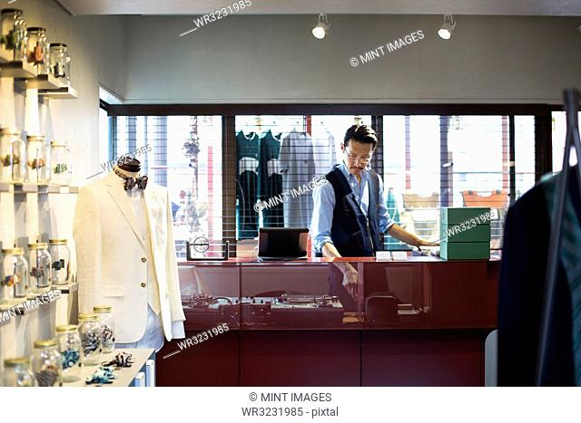 Japanese salesman with moustache wearing glasses standing at counter in clothing store