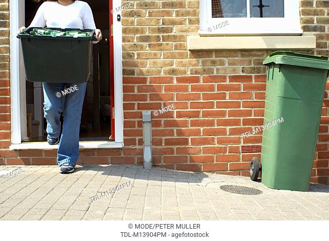 A woman putting out a box of recycling