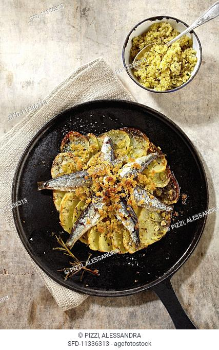 Sardines with salt crumble on fried potatoes (seen from above)