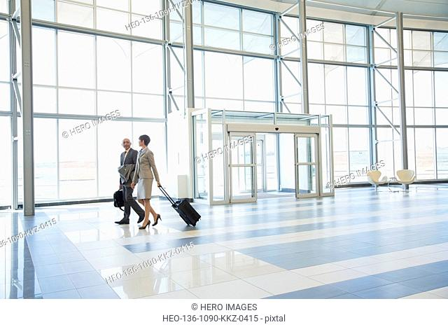 Business people with suitcases in modern lobby