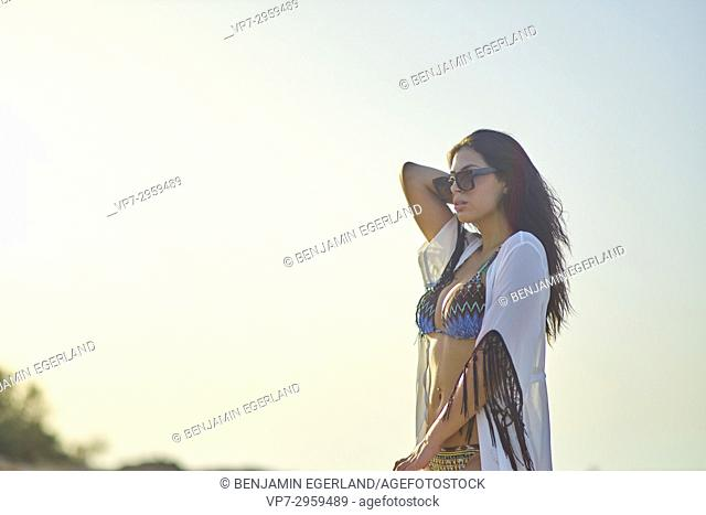 young cool woman with sunglasses in bikini enjoying evening sun. Greek ethnicity. In holiday destination Hersonissos, Crete, Greece