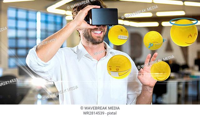 Happy man looking at emojis on VR glasses
