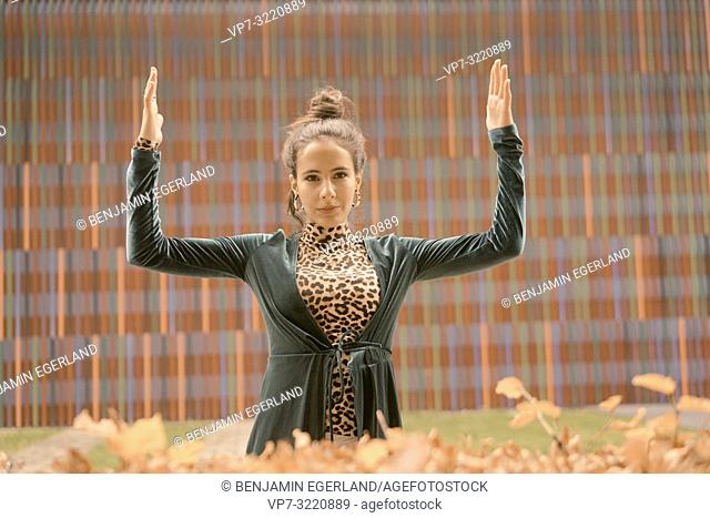 fashionable woman balancing hands, equated, balanced, in front of geometrical line pattern, in Munich, Germany