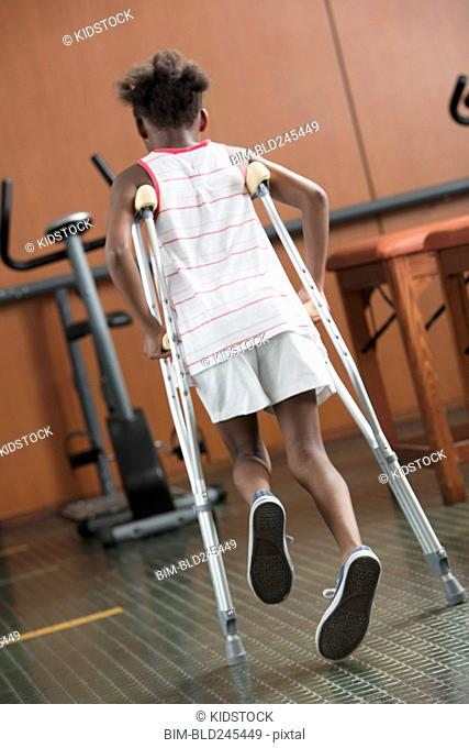 Black girl walking with crutches