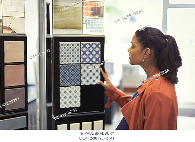 Woman browsing tile samples in home improvement store