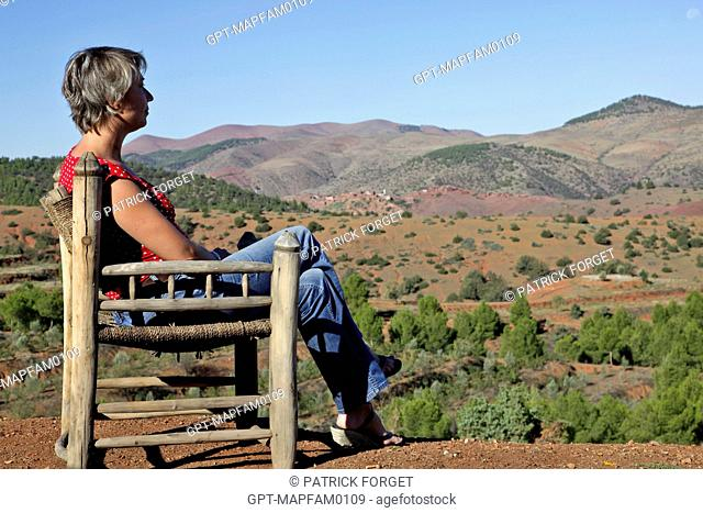 WOMAN ON VACATION ENJOYING THE PANORAMIC VIEW FROM THE FARM AT THE DOMAINE DE TERRES D'AMANAR, TAHANAOUTE, AL HAOUZ, MOROCCO