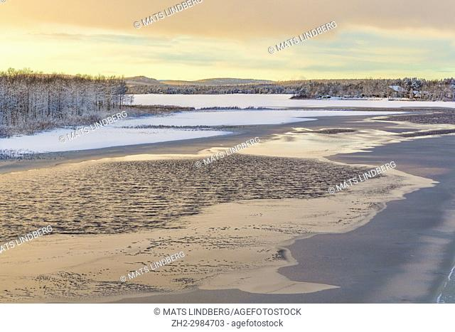 Frozen river in sunset with little open water and sky reflecting making nice colors in the water, mountains in background, Gällivare, Swedish Lapland, Sweden