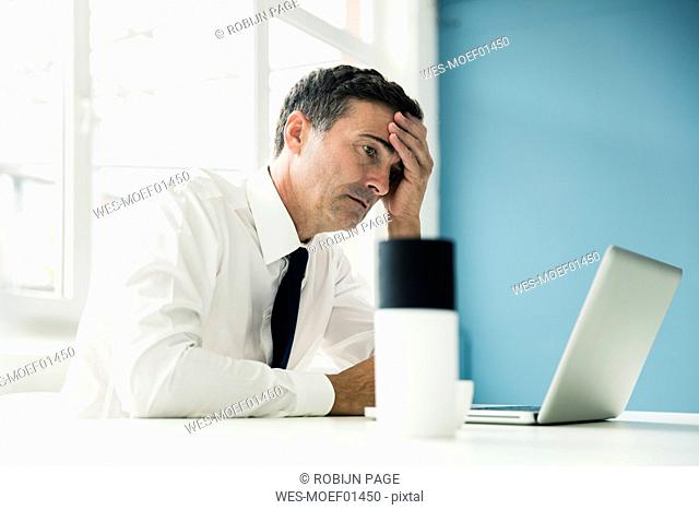 Serious businessman looking at laptop on table in office