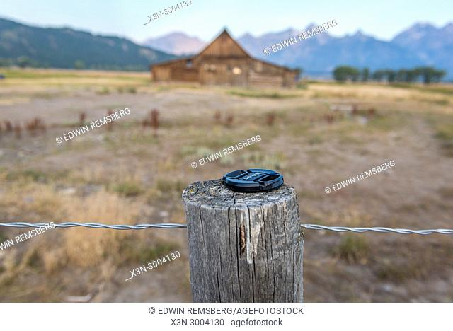 Lens cap placed on wooden fence post in front of T. A. Moulton Barn, Grand Tetons National Park, Teton County, Wyoming. USA