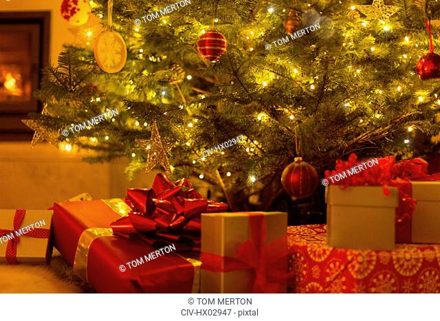 Gifts with red bows under illuminated Christmas tree