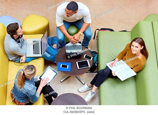 Overhead view of four male and female students brainstorming in higher education college study space