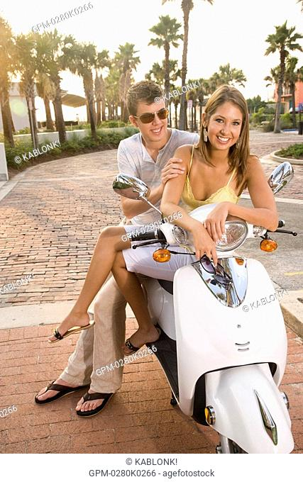 Portrait of young couple sitting on parked motor scooter on brick road