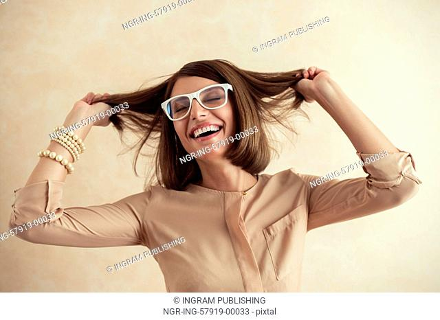 Happy excited woman dancing cheerful with wind in the hair on beige background