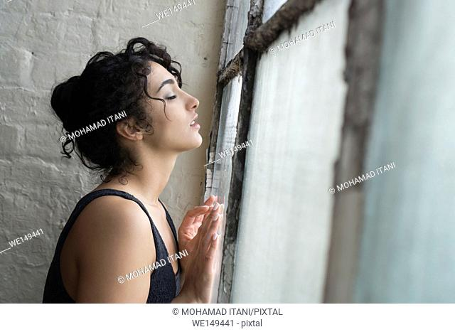 Young woman leaning against the window
