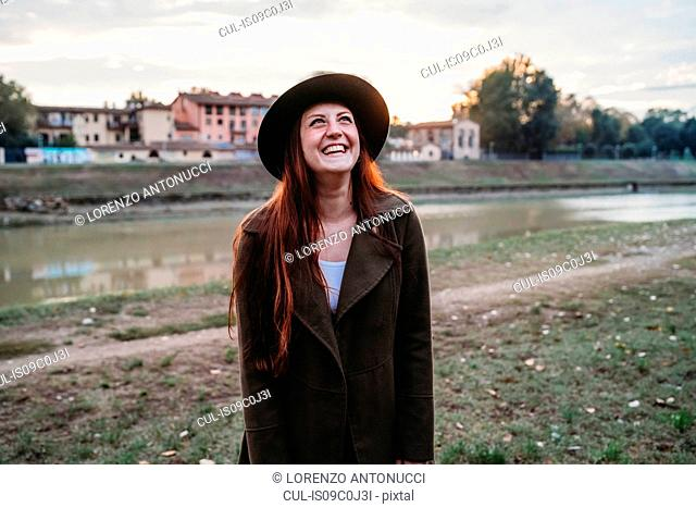 Young woman with long red hair laughing on riverside, Florence, Tuscany, Italy