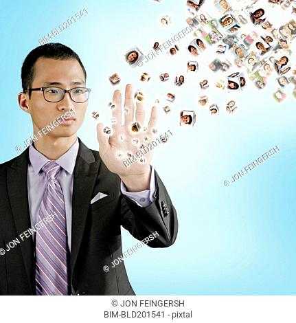 Asian businessman holding hand out to digital images