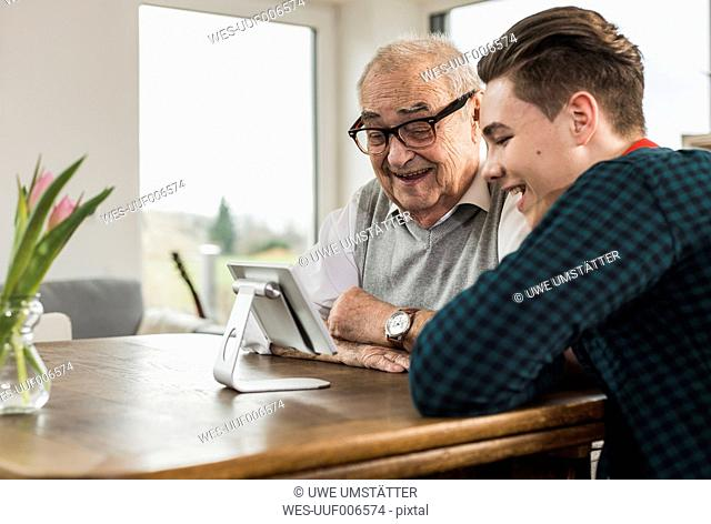 Happy senior man and his grandson looking at mini tablet