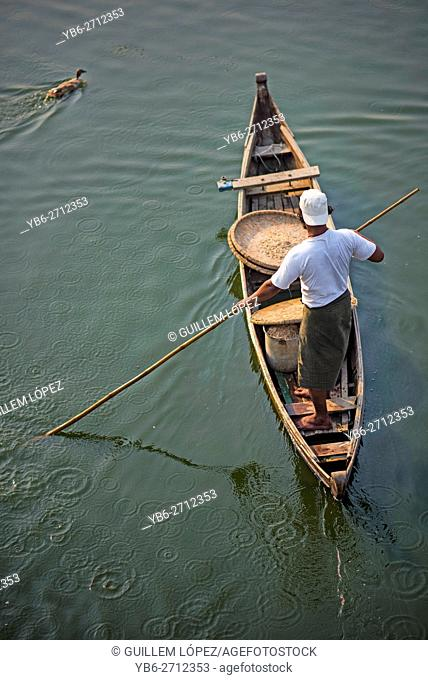 A duck herder in his boat at Taungthaman Lake, Amarapura, Myanmar