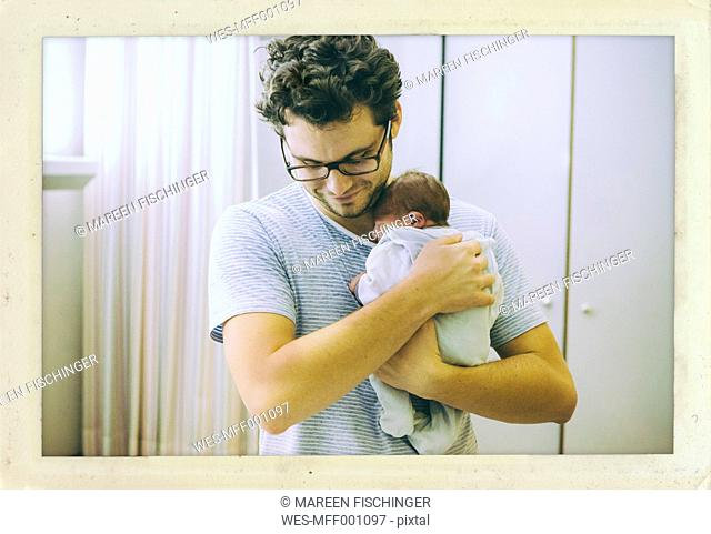 Father holding his newborn baby in hospital room