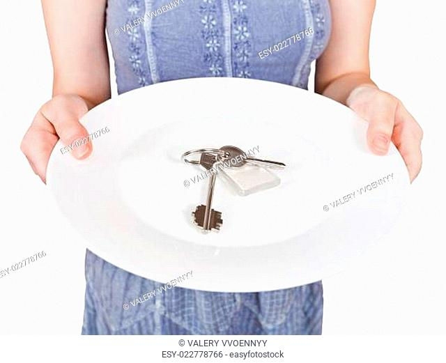 woman holds white plate with door keys