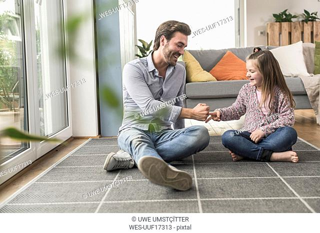 Young man and little girl sitting at home, playing paper scissors stone
