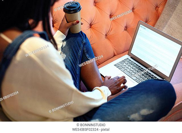 Young woman sitting on the couch with coffee to go using laptop