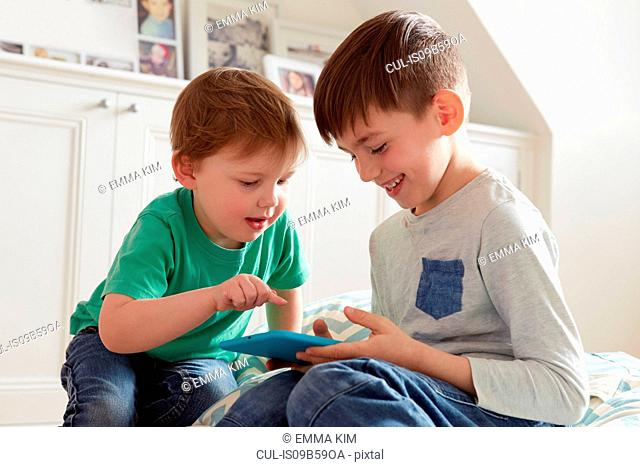 Male toddler and brother looking at digital tablet