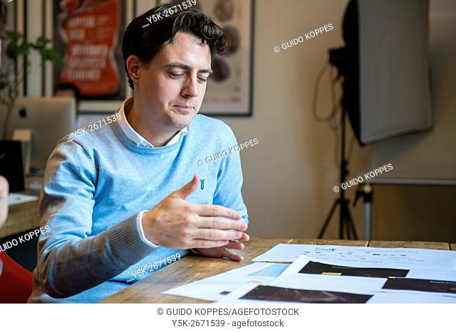 Utrecht, Netherlands. Young, professional male explaining his work during an interview on the Hart Island Project website