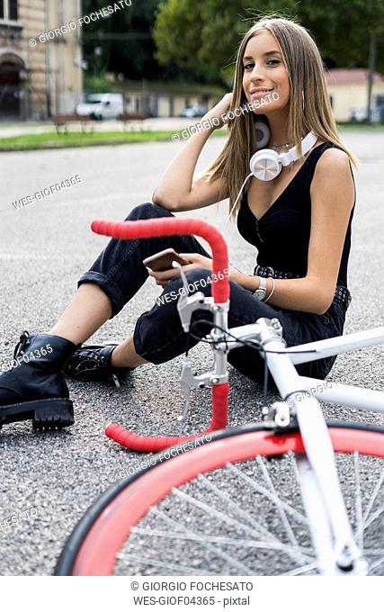 Smiling teenage girl sitting down holding cell phone next to bicycle