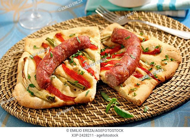 Savory pastry with sausages and vegetables. Coca de recapte