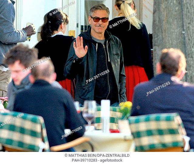 US actor George Clooney waves as he attends a barbecue at the hotel 'Zu den Rothen Forellen' in Ilsenburg, Germany, 21 May 2013