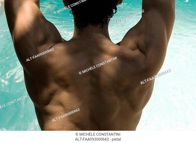 Man's muscular back, water in background