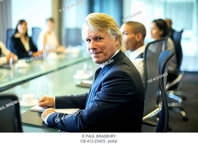 Portrait of businessman sitting at conference table in conference room