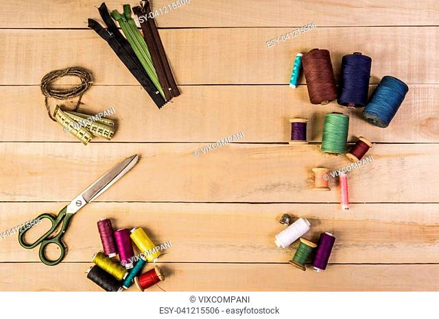 Thread for sewing different colors scissors zipper for clothes lie on a wooden table