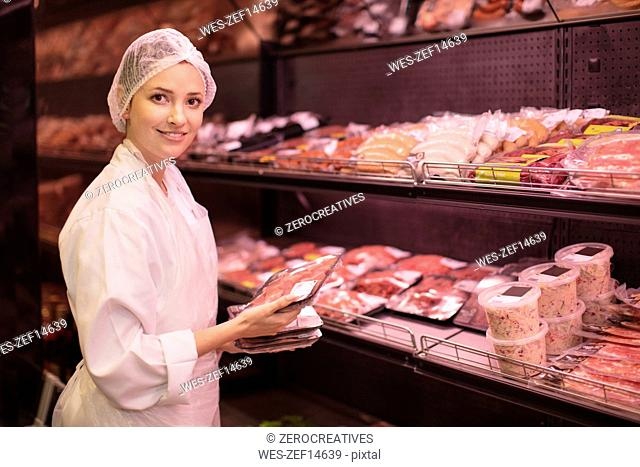 Portrait of smiling woman placing meat in display areas