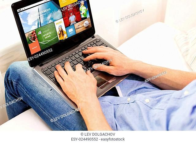 technology, internet, media, people and lifestyle concept - close up of male hands typing on laptop computer with news web page on screen keyboard at home