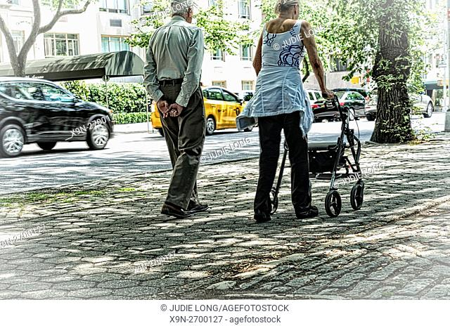 Unidentifiable Elderly Couple Walking Along a New York City Street. Woman Using and Pushing a Walker