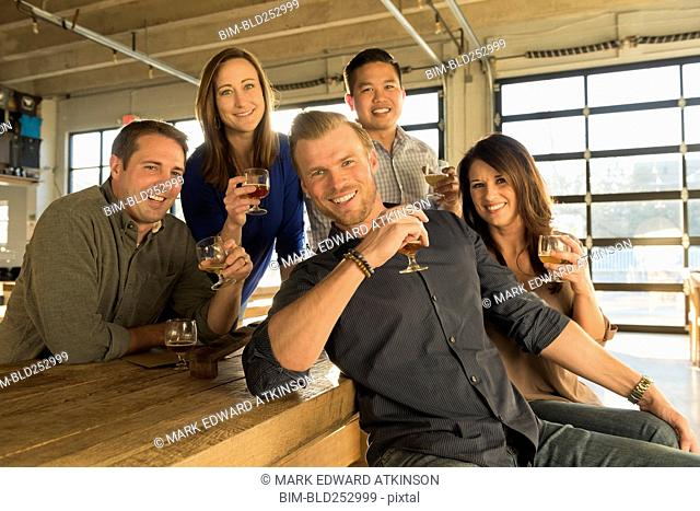 Portrait of smiling friends drinking beer in brew pub