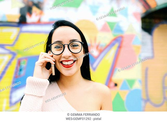 Portrait of happy woman on the phone in front of graffiti wall