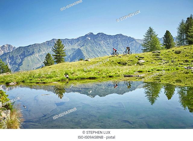 Young couple mountainbiking down hill, Karthaus, Val Senales, South Tyrol, Italy