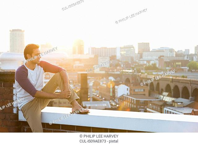 Man sitting on wall on rooftop, Birmingham, England, UK