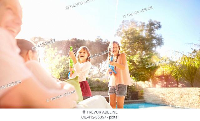 Playful sisters with squirt guns spraying water at sunny summer poolside