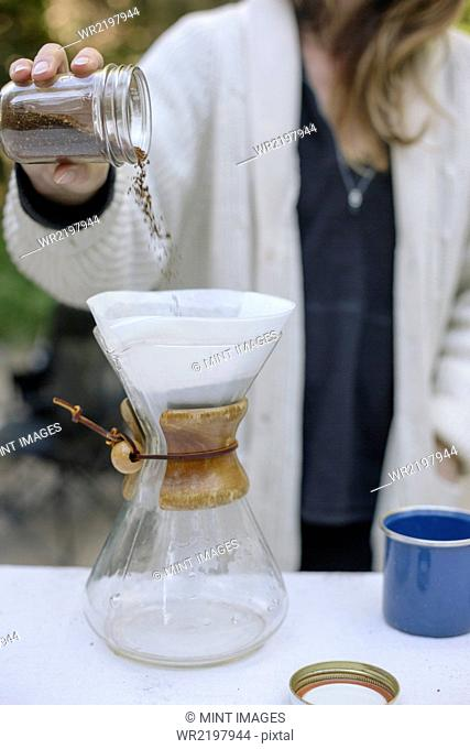 Woman pouring ground coffee from a jar into a glass coffee maker