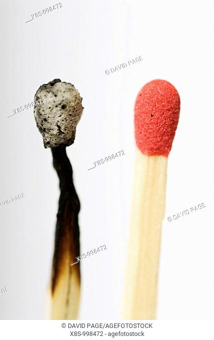 Stock photo of a live red match head next to an old burnt out match head  Conceptual image to illustrate before, after - old, new - change, dare to be different