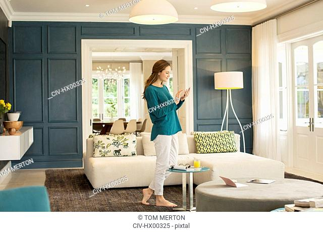 Woman texting with cell phone in home showcase living room