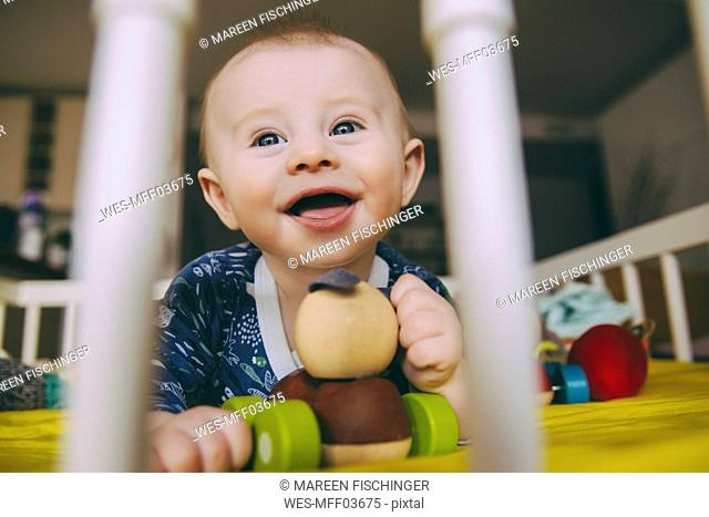 Portrait of happy baby boy with wooden toy in his crib