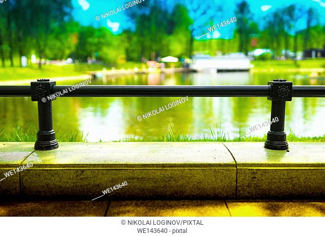 Horizontal park fence with lake bokeh background