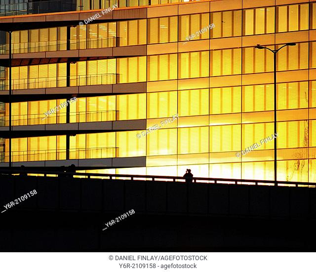 """A photographer at work on London Bridge in the heart of London, England, as warm evening light reflects on an office in the """"""""City"""""""" business district"